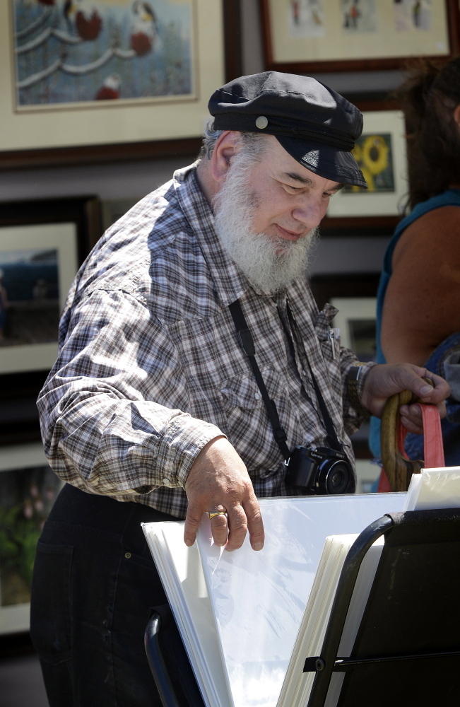 Allen Davis of Scarborough looks over artwork during Art in the Park at Mill Creek Park.