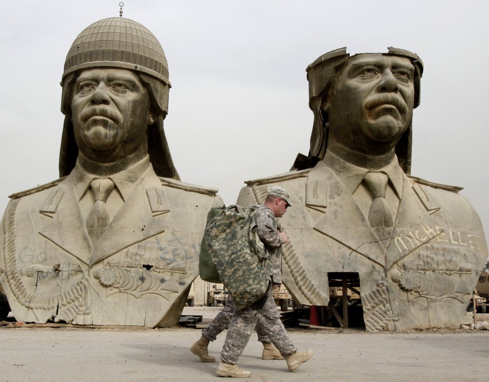 U.S. Army soldiers pass bronze busts of former Iraqi President Saddam Hussein in Baghdad in March 2009. Military and intelligence leaders from Saddam's regime now dominate the Islamic State group's top command, according to senior Iraqi officers.