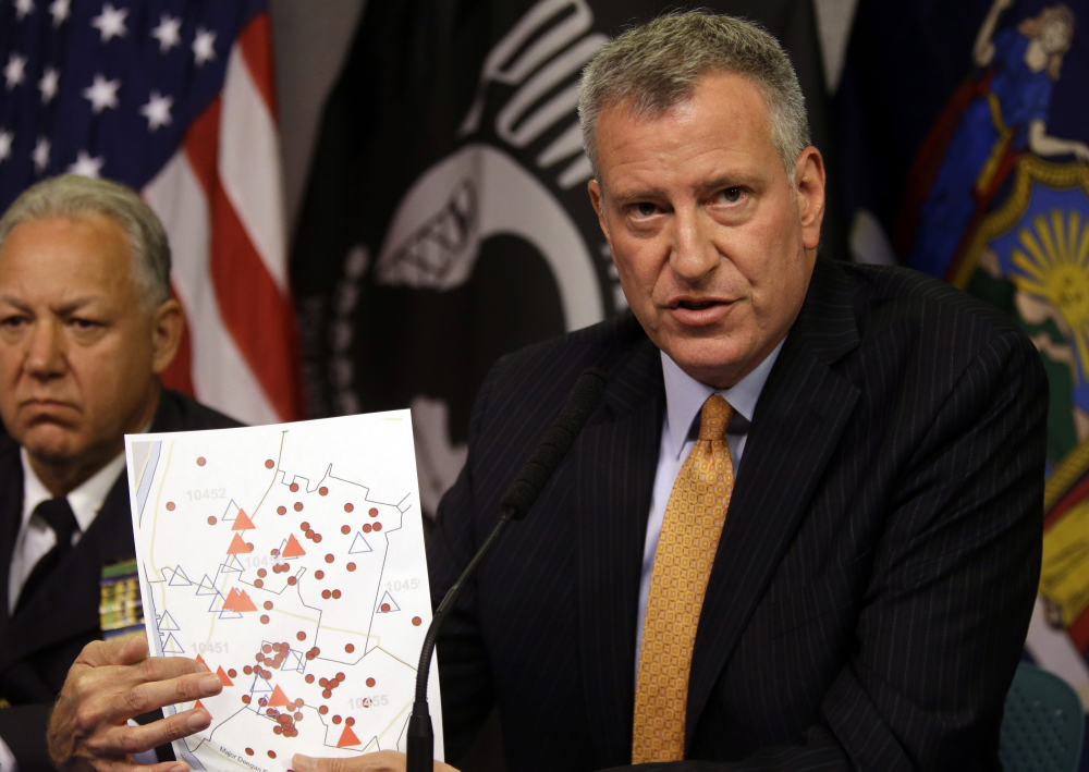 New York City Mayor Bill de Blasio holds a map showing the location in the Bronx borough of cooling towers, red triangles, and people, red dots, that were infected with Legionnaires' disease.