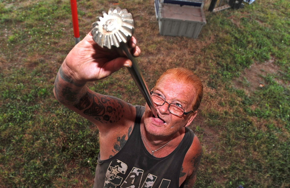 """Sword swallower John """"Red"""" Stuart swallows a car axle as he and his fellow performers with World of Wonders prepare for the annual Skowhegan State Fair at the Skowhegan Fairgrounds on Tuesday."""