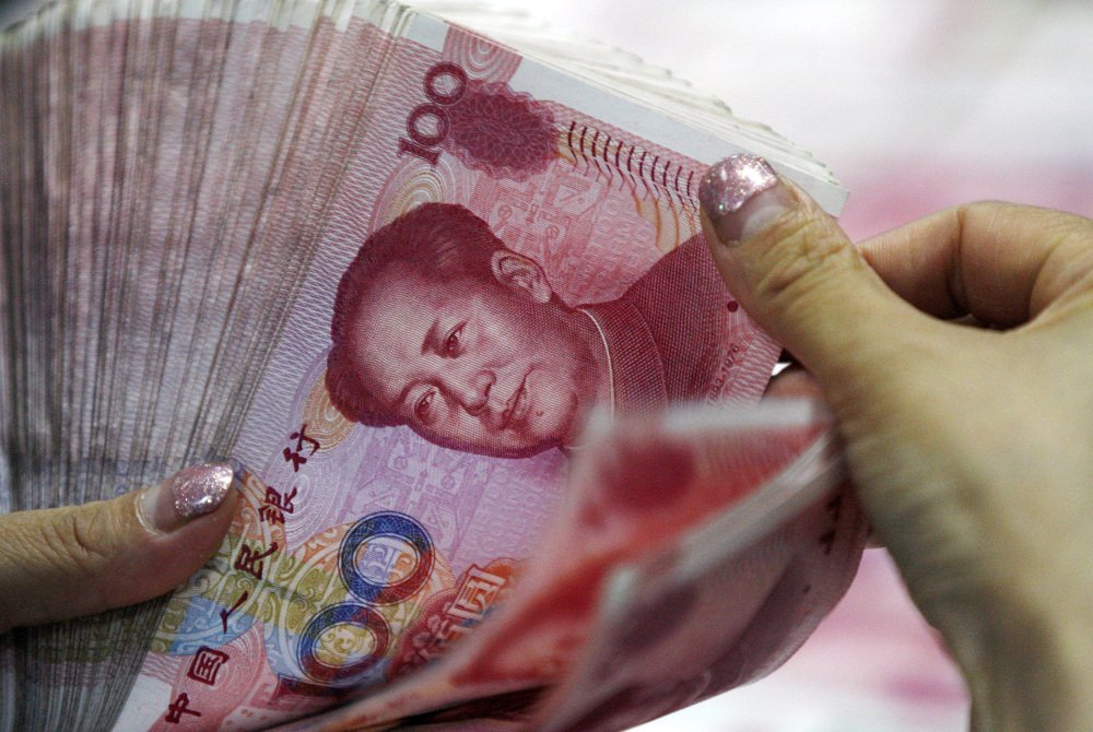 A bank clerk counts Chinese currency notes at a bank outlet in Huaibei in central China's Anhui province. The People's Bank of China said it will allow markets a greater role setting its value.