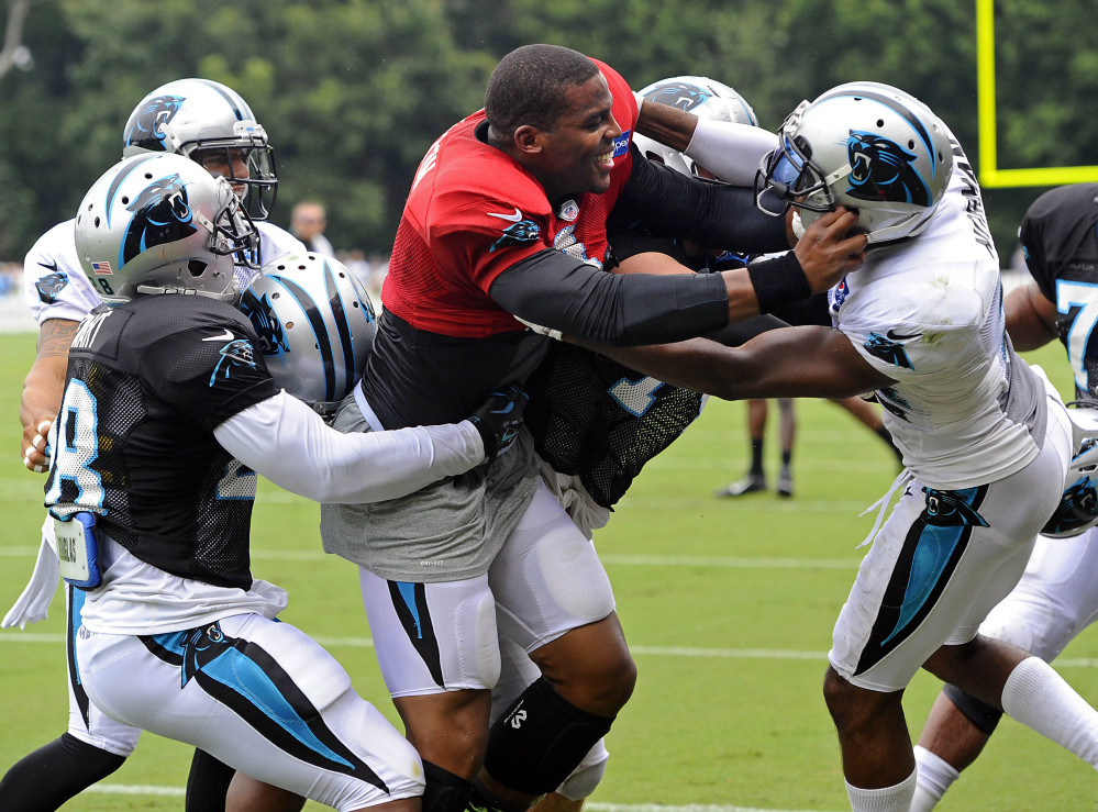 Cam Newton, center, wears the red jersey quarterbacks wear in practices, meaning they can't be touched. But that didn't stop him from going after cornerback Josh Norman, right, after taking a stiff-arm in a Carolina practice. And Newton said he'd do it again.