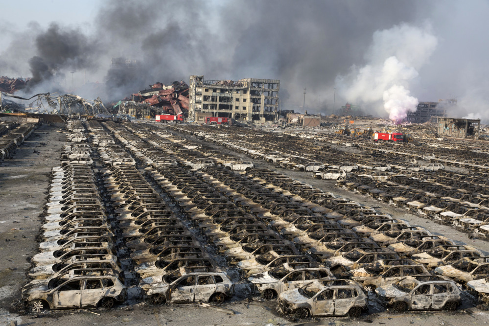 Smoke billows Thursday from the site of an explosion that reduced a parking lot filled with new cars to charred remains in northeastern China's Tianjin municipality. Huge explosions in the warehouse district sent up massive fireballs that turned the night sky into day, officials and witnesses said Thursday.