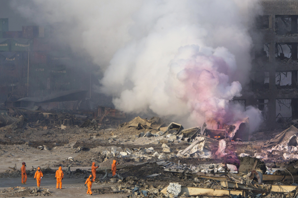 Firefighters in protective gear watch partially pink smoke billow after Wednesday's explosion. Huge, fiery blasts at a warehouse for hazardous chemicals killed at least 50 people and turned nearby buildings into skeletal shells, raising questions Thursday about whether the materials had been properly stored.