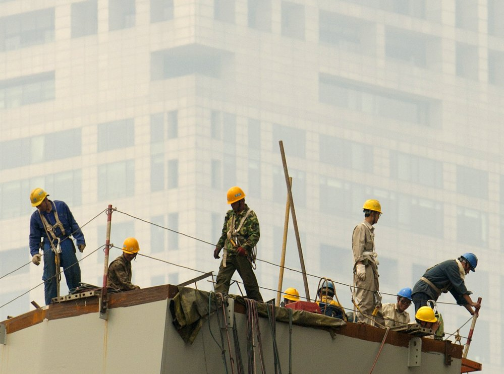 """Laborers work during a smoggy day in Beijing. The lead author of a new study says 38 percent of the Chinese population lives in an area with a long-term air quality average that the U.S. Environmental Protection Agency calls """"unhealthy."""""""