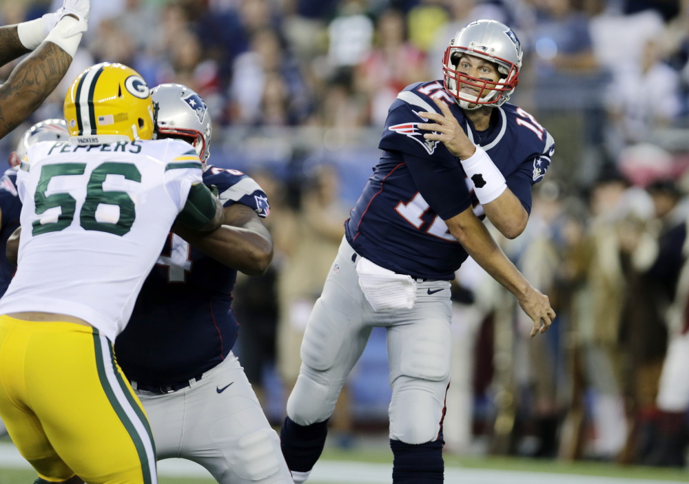 New England Patriots quarterback Tom Brady follows through on a pass over Green Bay Packers outside linebacker Julius Peppers in the first half of the Packers' 22-11 preseason win Thursday in Foxborough, Mass.