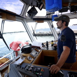 John Reeves, 29, captain of the tugboat Andrew McAllister, steers into Portland Harbor on his way to undock a ship. Portland Tugboat, part of New York-based McAllister Towing & Transportation, operates the port's tugs. Derek Davis/Staff Photographer