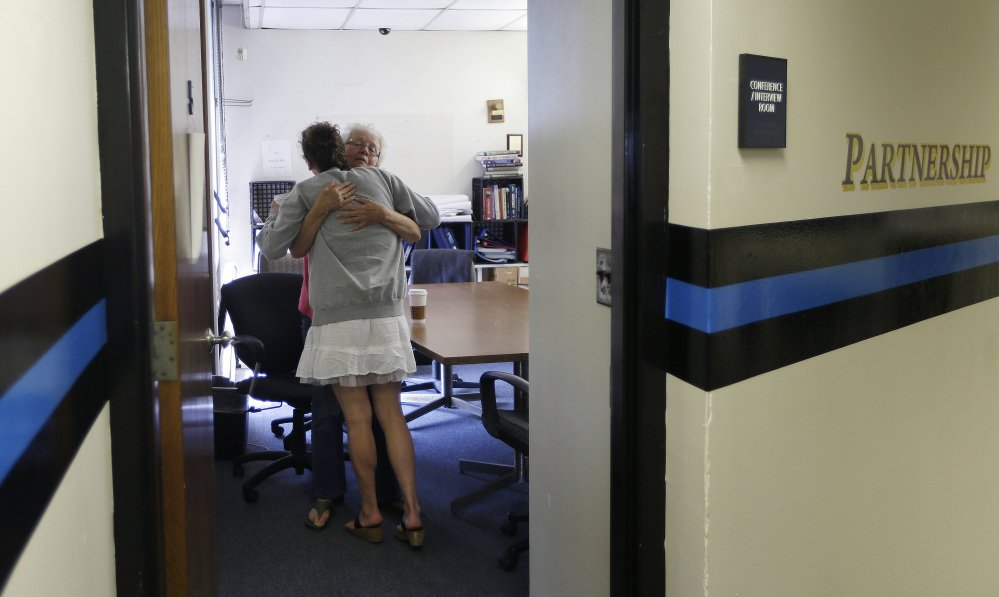 Inside the police station in Gloucester, Mass., volunteer Ruth Cote, facing, hugs a woman who has voluntarily come to the police for help kicking her heroin addiction. Gloucester is taking a novel approach to the war on drugs.