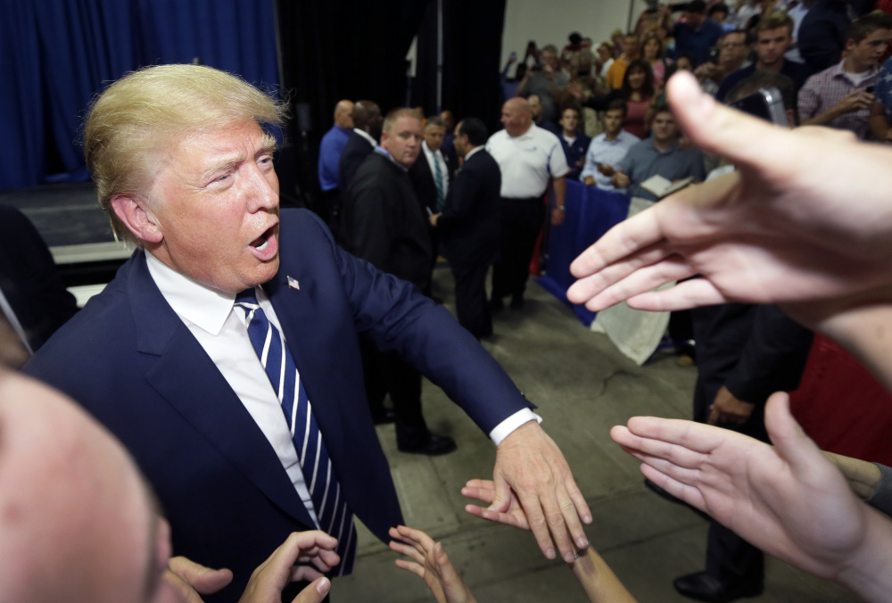 Donald Trump meets supporters after addressing a Republican fundraising event Tuesday in Birch Run, Mich. Trump says he wants to change environmental regulations to build a giant wall on the border with Mexico.