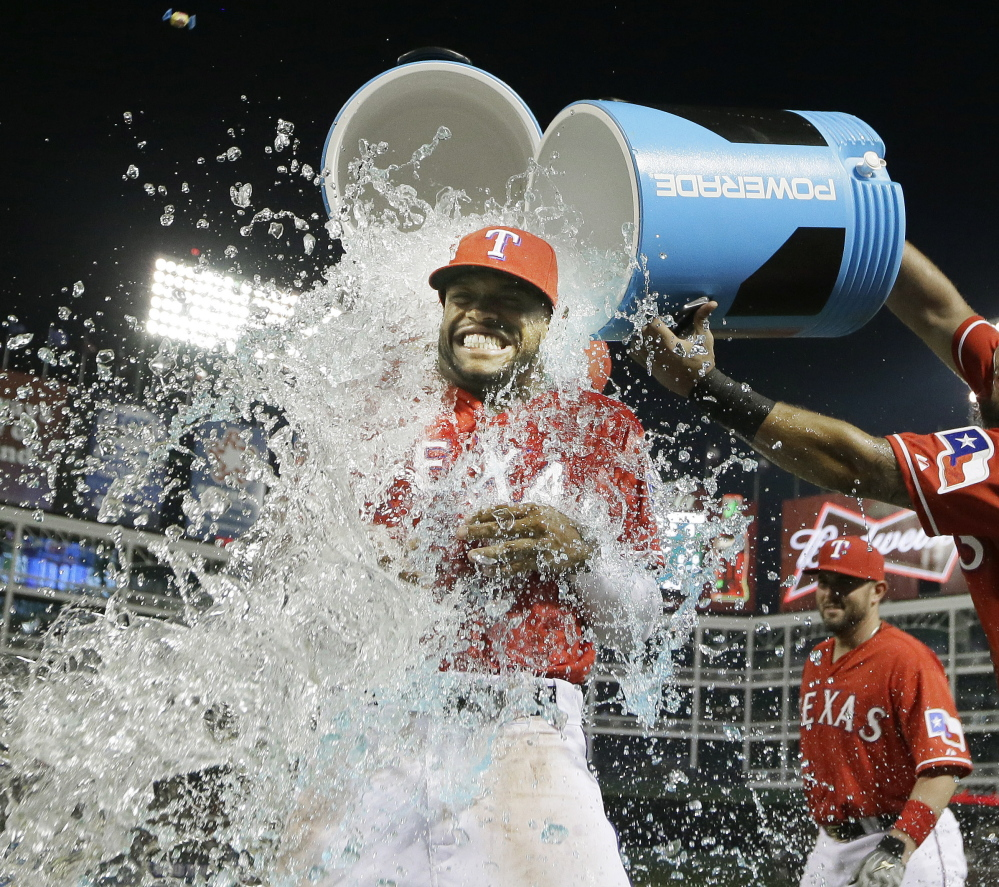 Delino DeShields of the Texas Rangers gets doused by teammate Rougned Odor after Texas beat the Tampa Bay Rays 5-3 Friday at Arlington, Texas.