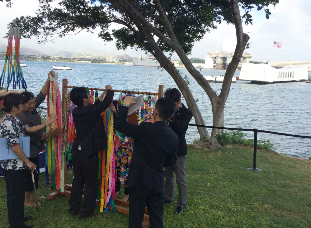 People hang paper cranes folded for peace near a memorial to the sunken battleship USS Arizona before a ceremony marking the 70th anniversary of the end of World War II, on Friday