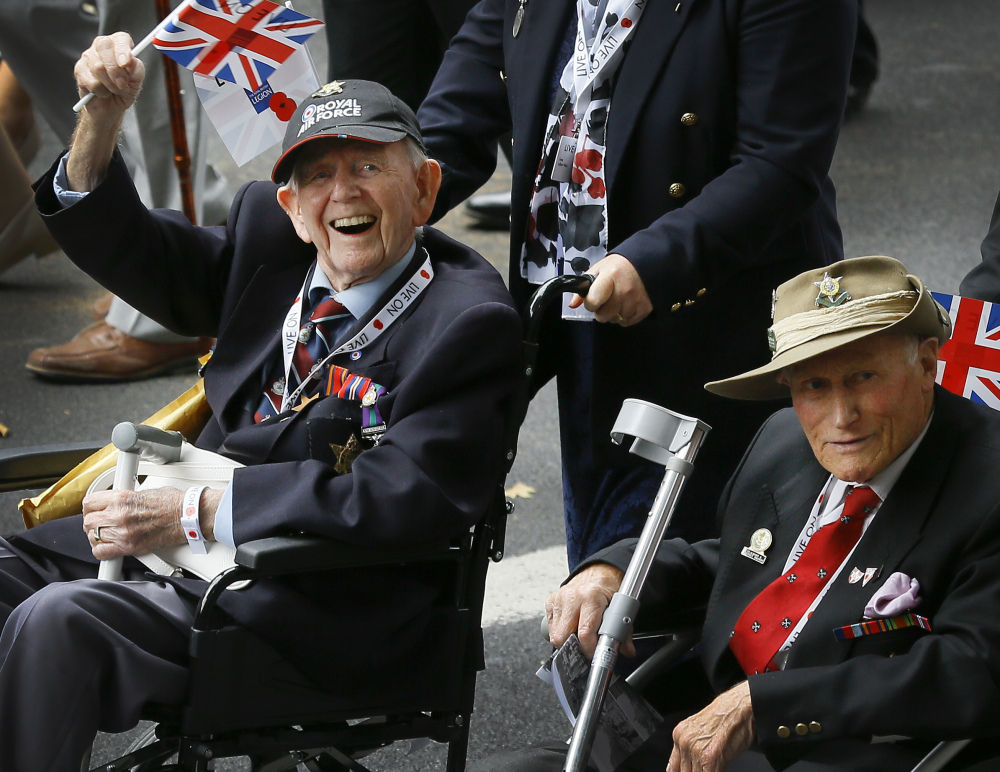 A veteran waves a flag during the parade to commemorate VJ day, as the parade passes along Whitehall in London on Saturday. Thousands cheered on the veterans of Britain's 4  -year campaign in Asia.