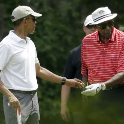 President Barack Obama  hands a ball to Vernon Jordan while golfing Saturday at Farm Neck Golf Club in Oak Bluffs, Mass., on the island of Martha's Vineyard.