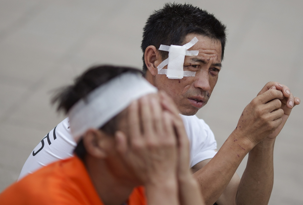 People injured in a huge explosion in Tianjin, China, pass the time at the school turned into a shelter for the evacuated. The blasts Wednesday night killed at least 112 people.