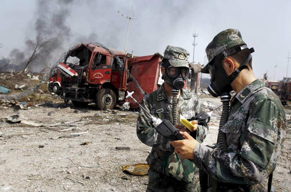 Soldiers of the People's Liberation Army anti-chemical warfare corps work next to a damaged firefighting vehicle at the site of Wednesday night's explosions in Tianjin, China.