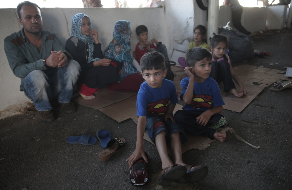 Migrant brothers Youssef Ahmed Zaid, 5, center, Muslim Ahmed Zeid, 3, from Afghanistan, wait with their family at a bus station until they can cross into Greece. Like many trying to cross the Aegean Sea, they seek asylum in Europe.