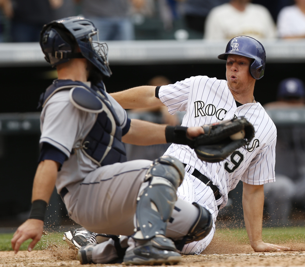 Colorado's DJ LeMahieu slides past the tag of San Diego catcher Austin Hedges in the seventh inning of the Rockies' 5-0 win Sunday in Denver.