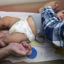 "Pediatrician Charles Goodman vaccinates 1-year-old Cameron Fierro in Northridge, Calif., in January, after explaining the need for the immunization to the boy's father. Maine's highest court last week ruled that state officials can have a year-old child in their custody immunized. His mother objects, saying she does ""not believe in viruses."""
