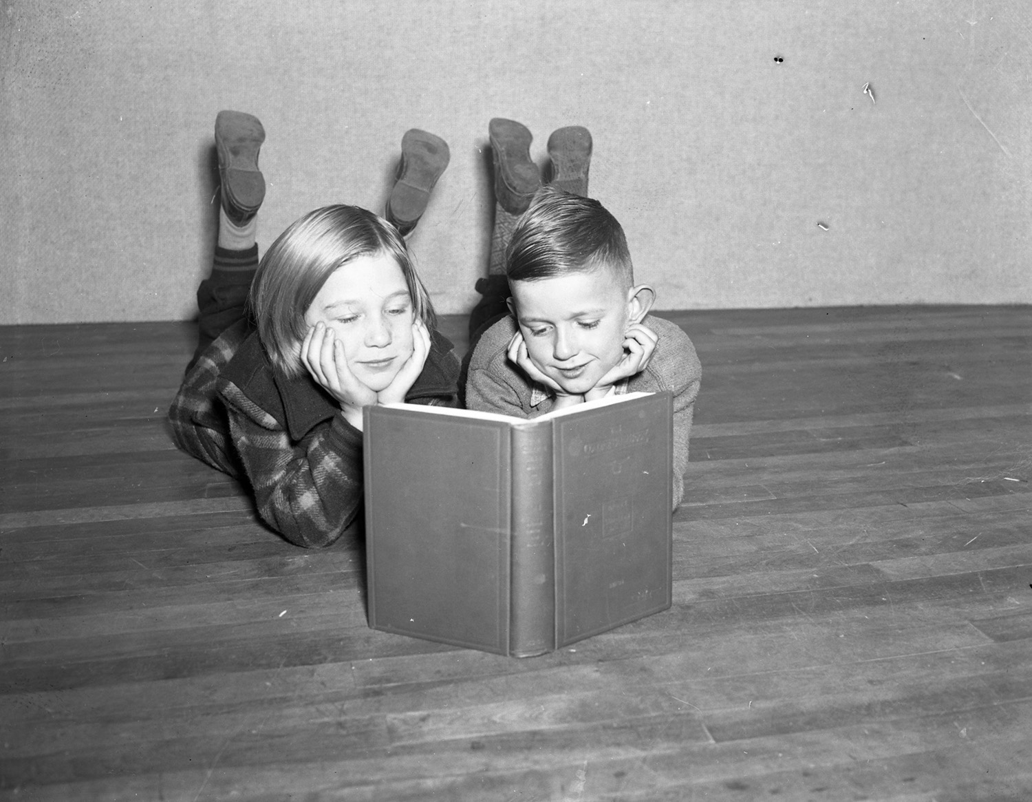 Greta Lawrence and Robert Burns read the same book, Nov. 13, 1937. From the Portland Public Library archival collection of Portland Press Herald, Maine Sunday Telegram and Evening Express photos.