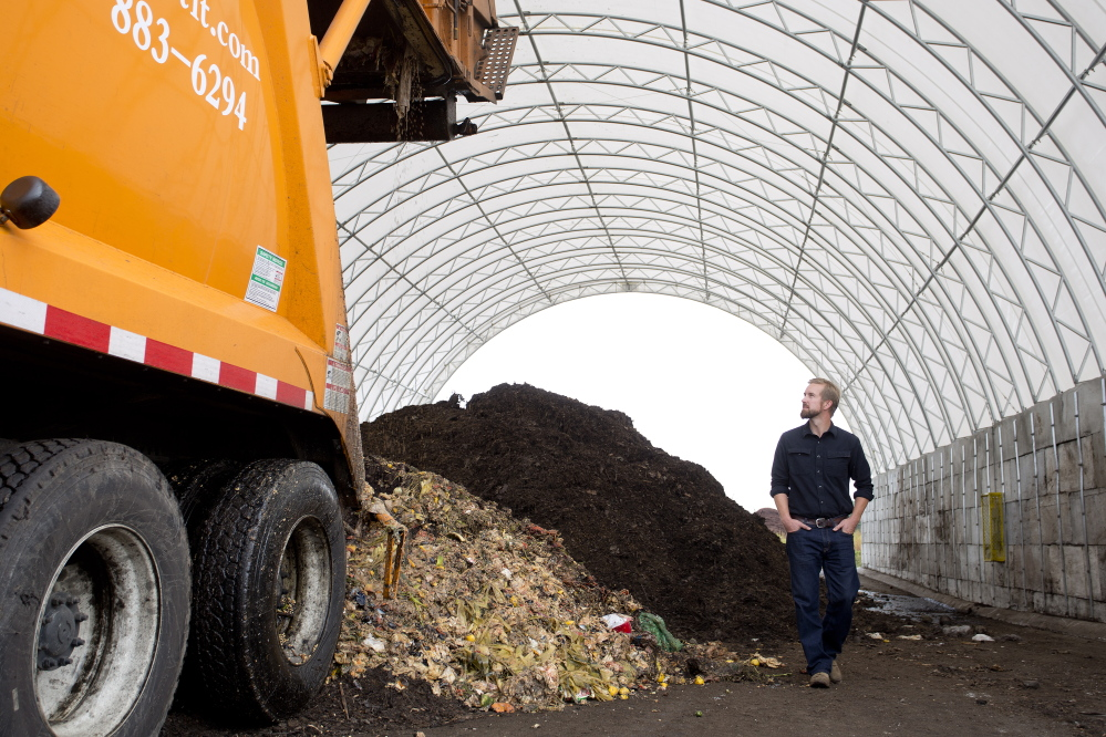 Brett Richardson of We Compost It! watches as his truck, operated by Emily Seluta (not pictured), dumps food waste into a large structure at CPRC Group in Auburn. The waste will be turned into compost.