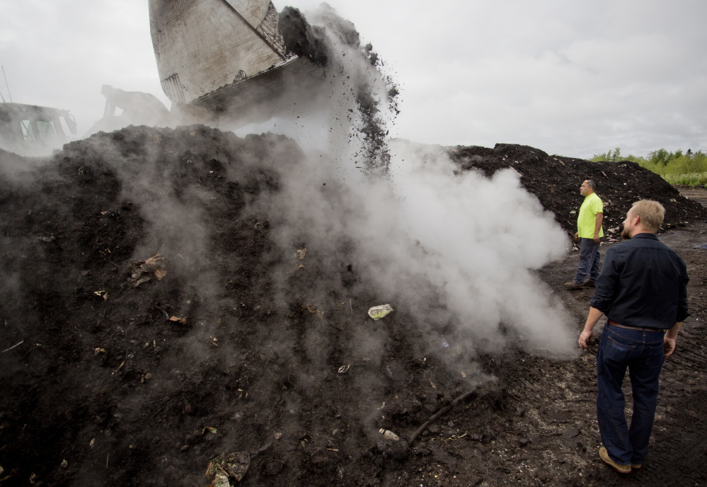 Leo Amara, of debris recycler CPRC Group, and Brett Richardson of We Compost It! watch as an excavator turns compost at a facility in Auburn. The compost cooks at about 160 degrees, causing steam to release when it is turned.