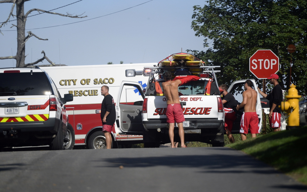 Lifeguards and rescue personnel gather at the end of Dune Avenue in Saco while responding to reports of people caught in rip currents Monday.