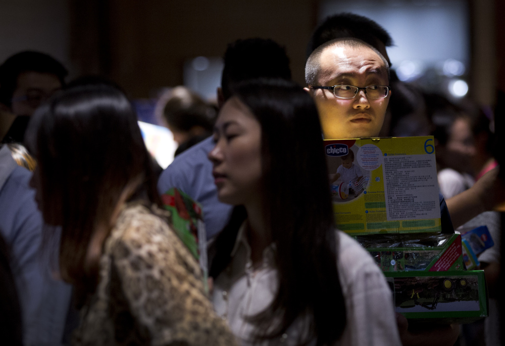 A man waits in line near a cashier counter at a shopping mall in Beijing. China is trying to engineer an economic transition from rapid growth fueled by exports and often-wasteful investment to slower growth built on consumer spending.