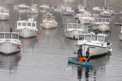 With sternman Kyle Draper, left, Josh Audet paddles his skiff back to dock after mooring his lobster boat, Karamel, in Perkins Cove after a day of lobstering Thursday. Gregory Rec/Staff Photographer