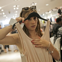 Sofia Harrison, 15, holds up a top while shopping at Roosevelt Field mall in Garden City, N.Y. More teens are thrifty nowadays, a habit picked up from their recession-scarred parents.