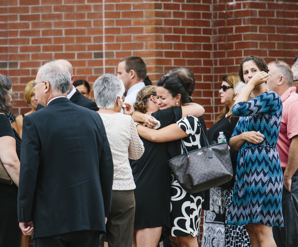 Family, friends and members of the Saco community embrace after services for Wendy Boudreau at Thornton Academy in Saco on Tuesday.