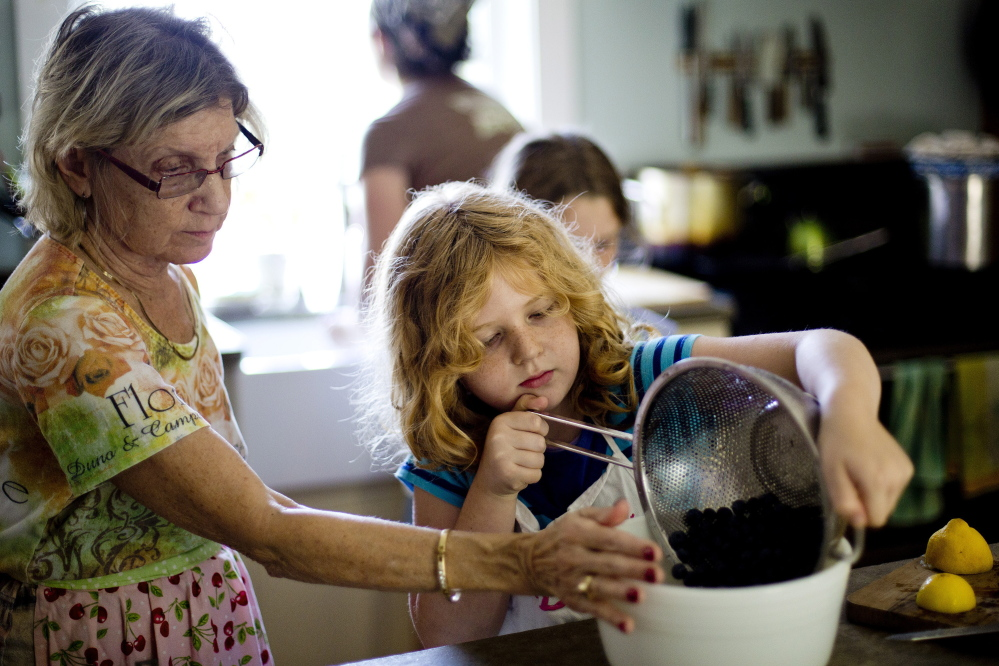 Nancy Schatz helps her granddaughter Beatrice Schatz, 7, dump berries from a colander into a mixing bowl as they prepare the filling for Schatz's prizewinning blueberry pie at the home of Karl Schatz and Margaret Hathaway and their daughters in Gray.