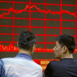 Chinese investors monitor stock prices at a brokerage house in Beijing on Tuesday, as China's main stock market index fell for a fourth day, plunging 7.6 percent to an eight-month low.