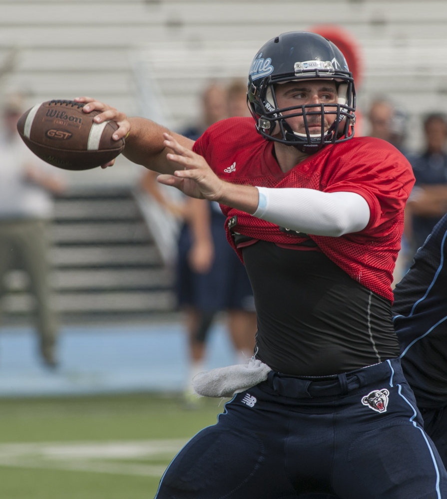 Maine football senior linebacker Cabrini Goncalves (2) fakes the handoff from quarterback Drew Belcher during scrimmage Tuesday, August 25, 2015, at Morse Field in  Orono, Maine.