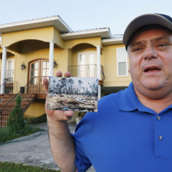 Efrem Garza stands before his new home built on the lot of his previous house that was destroyed by Hurricane Katrina. He holds a photograph taken by a friend showing the remains of his previous house on South Seashore Avenue in Long Beach, Miss. Before the storm Garza was surrounded by houses and trees, now 10 years later, there are only two houses on that land, as few of the residents returned and rebuilt.