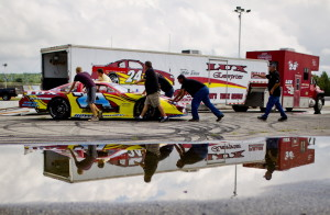 Numerous helping hands push Gunnar Rowe's stock car back to its trailer Wednesday. The 15-year-old Rowe will attempt to qualify for the Oxford 250 on Sunday.