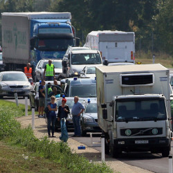 Police stand near a truck that  stands on the shoulder of the highway A4 near Parndorf south of Vienna, Austria, Thursday, Aug 27, 2015. At least 20 migrants were found dead in the truck parked on the Austrian highway leading from the Hungarian border, police said.