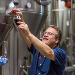Founder and owner Rob Tod takes beer off a fermentor at Allagash Brewing Co. The Clean Water Rule will help protect the high quality of water from the Sebago Lake watershed, the source for Portland-based Allagash.