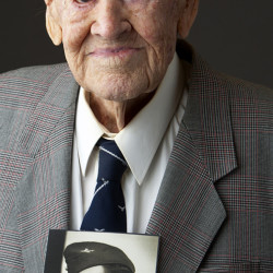 """Great Escape"" survivor Paul Royle poses holding a photo of himself in uniform during World War II."