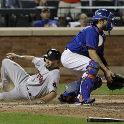 Blake Swihart slides past New York Mets catcher Travis d'Arnaud to score on an inside-the-park home run in the 10th inning Friday night in New York.