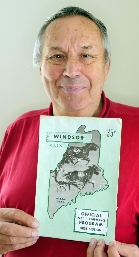 Eino Leinonen holds up a 1967 Windsor Fair racing program. He's attended every harness race at the fair for 47 years.
