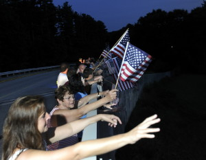 Well-wishers wave American flags while they wait on a Maine Turnpike overpass in Arundel on Saturday for a procession escorting the remains of Corey Dodge back to Maine. The Garland man was killed in Afghanistan last weekend. Story, B3