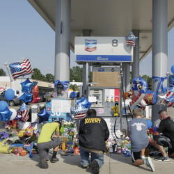 Mourners gather at a gas station in Houston on Saturday to pay their respects at a makeshift memorial for Harris County Sheriff's Deputy Darren Goforth who was shot and killed while filling his patrol car.
