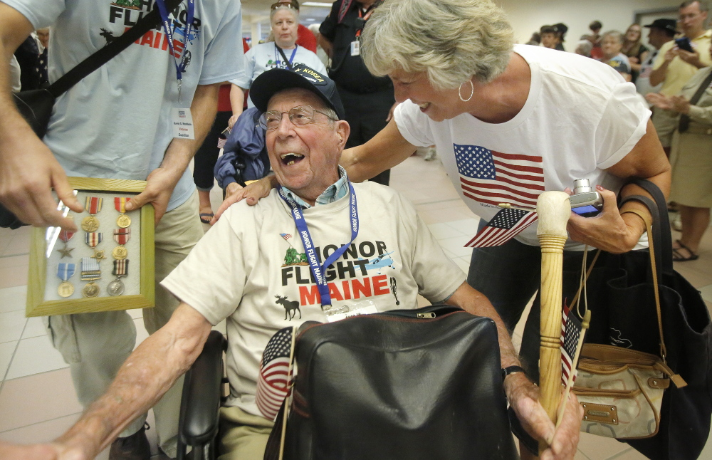 Veteran Henry Poisson of Turner is all smiles after getting a hug from his daughter, Cheryl Washburn, upon his return to Portland after an Honor Flight trip to Washington, D.C., on Saturday and Sunday. Poisson and 26 other veterans went on the free trip organized by Honor Flight Maine to visit memorials and Arlington National Cemetery. Poisson, 92, is a veteran of World War II and Korea and was awarded two Silver Star Medals and a Bronze Star Medal.