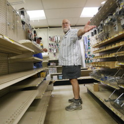 Butch Goff points out the few items that remain on the electrical shelves for his longtime customer Denny Landry, an electrician. Goff and his wife, Jean, are closing the store after 46 years.