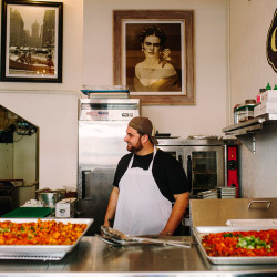 Otto Pizza District Manager Alex Budd works behind the counter at Ocho Burrito in Portland. The take-out restaurant opened Thursday.