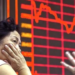 A Chinese investor monitors stock prices at a brokerage in Beijing on Wednesday. Asian stocks were mixed Wednesday and Shanghai's index fell despite Beijing's decision to cut a key interest rate to help stabilize gyrating financial markets and counter short liquidity. The Associated Press