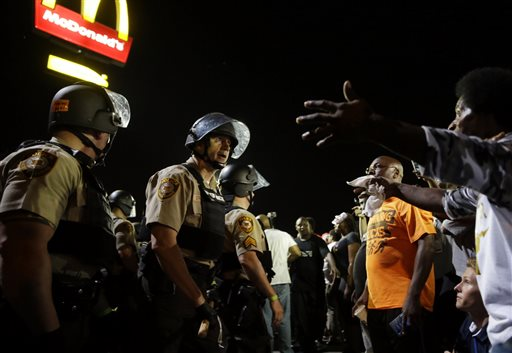 Officers and protesters face off along West Florissant Avenue, Monday in Ferguson, Mo. The Associated Press