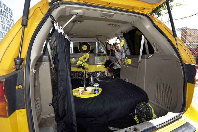 Airbnb renters Michael and Tabitha Akins, and their dog Bagheera, check their accommodations in a decommissioned 2002 Honda Odyssey yellow taxi, in New York City.