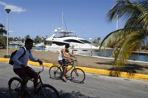 Cuban boys cycle past an American yacht moored at the Hemingway Marina in Havana, Cuba, Thursday. The elimination of all restrictions on nautical tourism appears to be eminent, says Jose Luis Perello, a tourism professor at the University of Havana. That won't just open the doors to Americans, but also to visitors from other countries and yacht clubs. The Associated Press