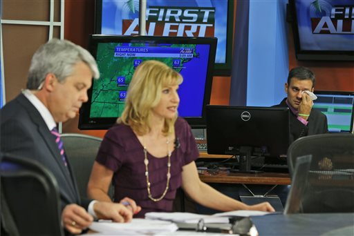 WDBJ-TV7 meteorologist Leo Hirsbrunner, right, wipes his eyes during the early morning newscast Thursday as anchors Kimberly McBroom, center, and guest anchor Steve Grant deliver the news at the station in Roanoke, Va. The Associated Press